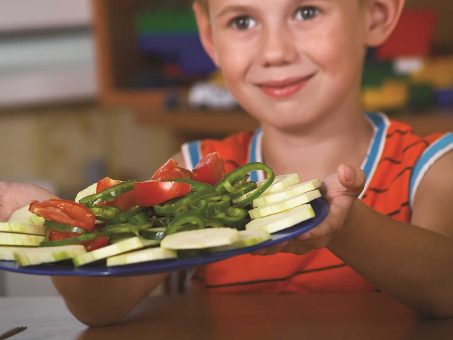 Kid Holding Plate Of Veggies