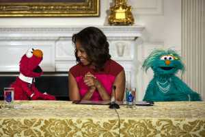 "First Lady Michelle Obama, with Sesame Street Muppets Elmo and Rosita, makes a ""Let's Move!"" announcement about marketing healthier foods to children, in the State Dining Room of the White House. (Official White House Photo by Lawrence Jackson)"