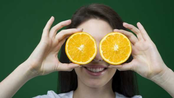 young lady goofing around with orange slices for eyes