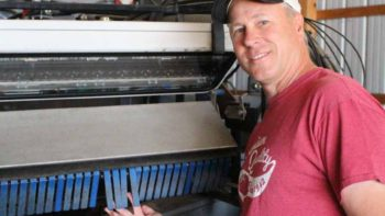 Jim Paarlberg of Paarlberg Farms points out how the Odenberg double sorters on his Pik Rite tomato harvester feature electronic fingers that can  accept or reject tomatoes.   Photo credit: Gabrielle Paarlberg