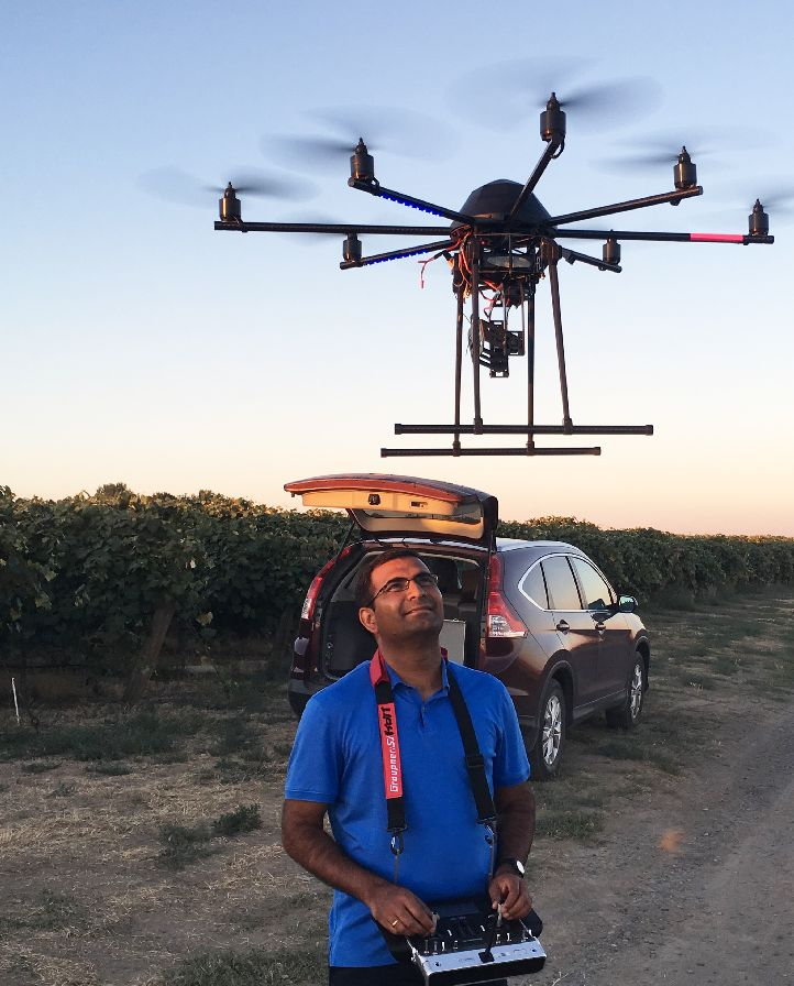 Washington State University Professor Lav Khot prepares to fly the 8-bladed octo-copter over a vineyard to measure how effectively a new irrigation method gets water to the vines. (Photo credit: WSU)