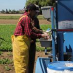 farmworkers using handwashing station