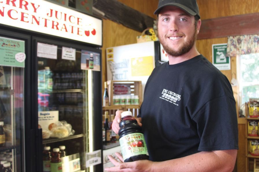 The King family bottles and sells tart cherry concentrate in their farm markets and online. Here, Jack King, poses with a bottle for sale in their retail market. (Photo credit: Christina Herrick)