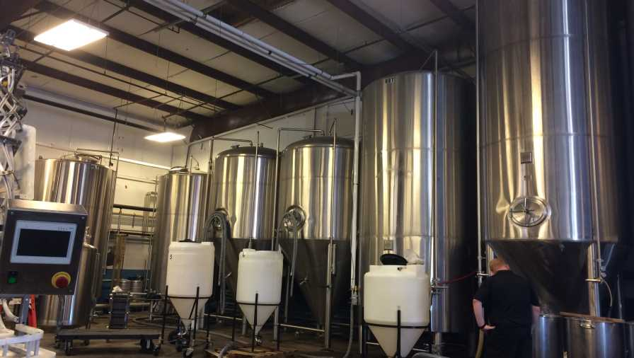 Vats of craft beer at 3 Daughters Brewing